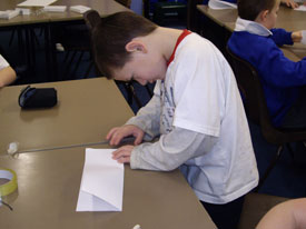 Making the first fold on a paper aeroplane.