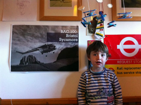 Luka with his poster of a Bristol Sycamore which has pride of place in his bedroom. Luka fell in love with helicopters when one landed in the park opposite the flats where he lives.
